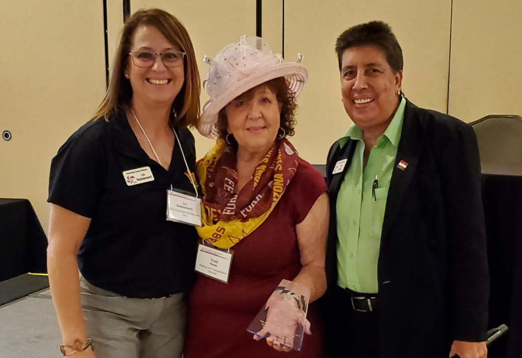 Trudy Perez, with a Crown Creations pink hat on between Liz Badalamenti, Membership Chair and Carol Comito UCW President.